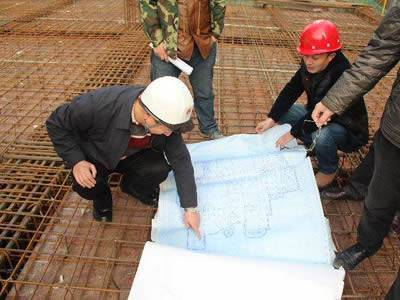 Workers are checking the position of steel bars according to the construction drawing.
