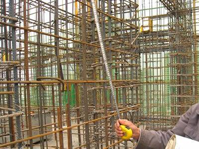 A worker is checking the spacing between reinforcing steel bars.
