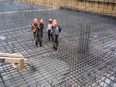Five workers are standing on the reinforcing rib mesh.