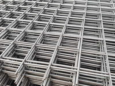 Many galvanized concrete reinforcing mesh with square opening placed together orderly.